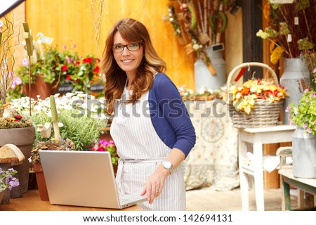 Smiling Mature Woman Florist Small Business Flower Shop Owner.  She is using laptop to take orders for her store. Shallow Focus.