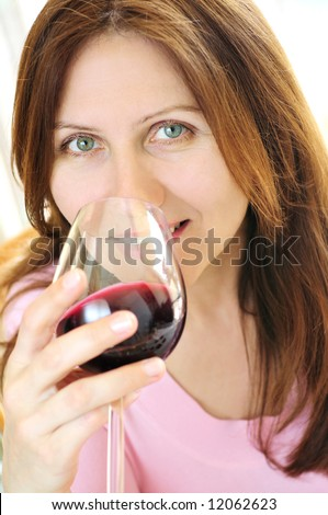 Smiling mature woman holding a glass of red wine