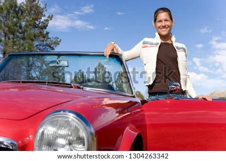 Smiling mature woman next to classic convertible car at camera