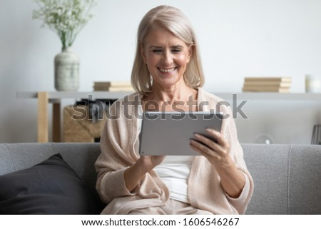 Smiling mature woman sit relax on sofa in living room enjoy watching movie on tablet at home, happy mature old female retiree use electronic gadget browse internet, read news, easy technology concept