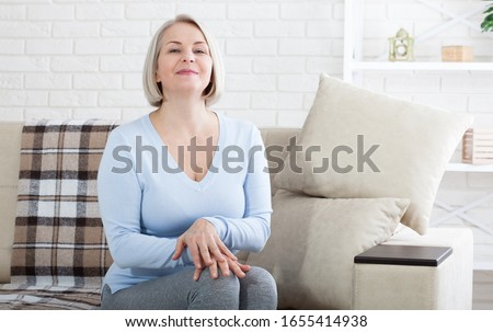 Smiling mature woman sitting on her sofa relax