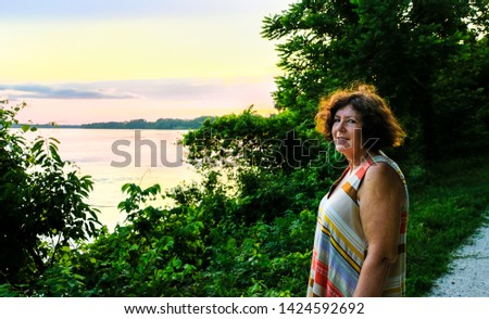 Smiling mature woman standing by Missouri River watching sunset