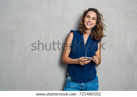 Smiling mature woman using smartphone and looking at camera. Happy woman typing on cellphone over gray background with copy space. Portrait of smiling latin woman messaging with smartphone.