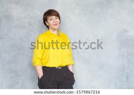 Smiling mature woman wearing yellow shirt standing on gray background