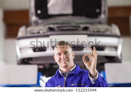 Smiling mechanic doing a gesture with his fingers in a garage