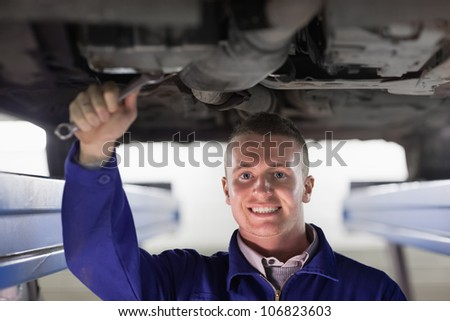 Smiling mechanic repairing a car with a spanner in a garage