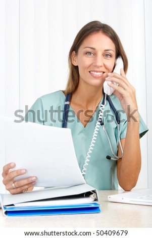 Smiling medical doctor with telephone. Over white background