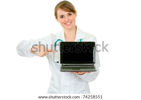 Smiling  medical doctor woman pointing finger on  laptop with blank screen  isolated on white