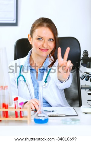 Smiling medical doctor woman sitting at office table and showing victory gesture