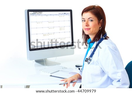 Smiling medical doctor woman with computer. Isolated over white background