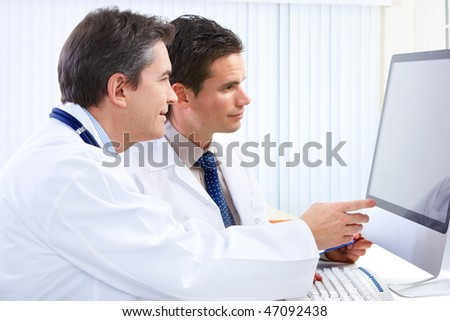 Smiling medical doctors with stethoscopes and computer.