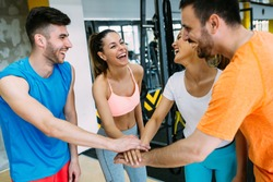 Smiling men and women doing high five in gym