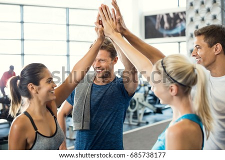Smiling men and women doing high five in gym. Group of young people making high five gesture in gym after workout. Happy successful fitness class after training. #685738177