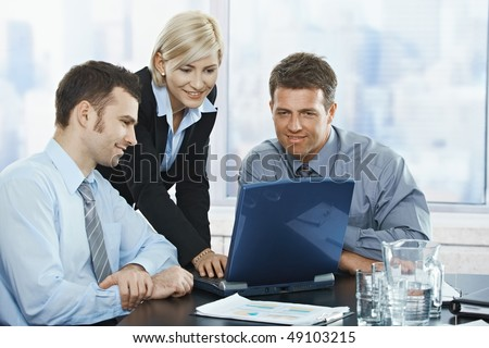 Smiling mid-adult businesspeople at meeting looking at laptop in office.