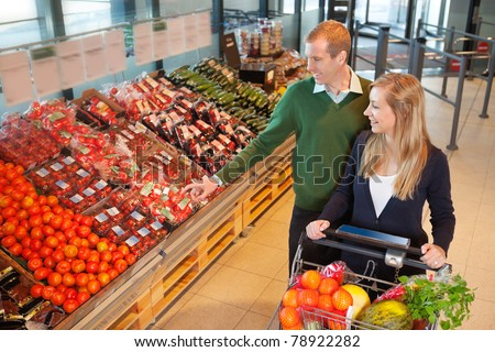 ... mid adult man pointing at vegetables while shopping with wife in grocery