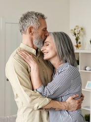 Smiling mid age older couple hugging and kissing standing at home. Happy senior adult mature classy husband and wife embracing, bonding, enjoying wellbeing and love in new modern house.