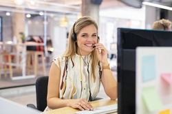 Smiling mid woman working as customer support operator with headset in a call center. Portrait of happy sales agent sitting at desk and looking at camera. Customer care support service representative.