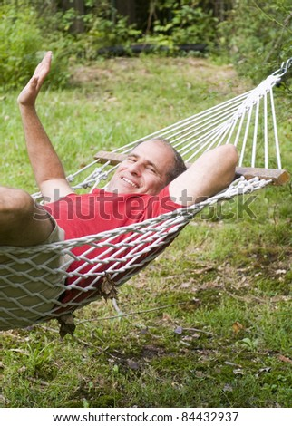 smiling middle age man relaxing in hammock in suburban backyard - stock photo