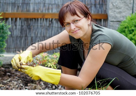 smiling middle age woman gardener with flowers outdoor in her garden