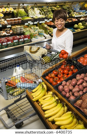 Smiling middle aged African American woman selecting tomatoes from grocery store produce.
