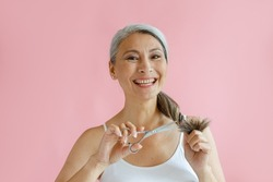 Smiling middle aged Asian lady cuts frayed ends of long silver hair with scissors on pink background in studio. Mature beauty lifestyle