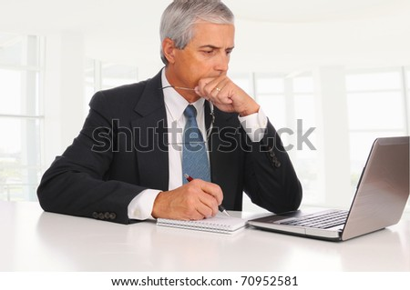 Smiling Middle Aged Businessman at desk using laptop computer with concerned expression in modern office.