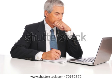 Smiling Middle Aged Businessman at desk using laptop computer with concerned expression isolated on white.