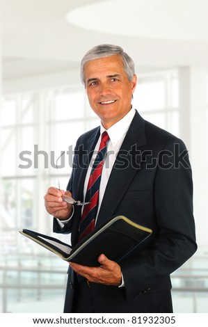 Smiling middle aged businessman holding a binder and his eye glasses while standing in an office lobby.