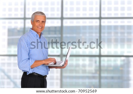 Smiling Middle Aged Businessman holding laptop computer with in front of large window in modern office.