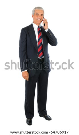 Smiling middle aged businessman in a suit and tie standing and talking on a cell phone with his other buy his side. Business man is in full  length over a white background.