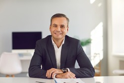 Smiling middle aged businessman in suit sitting and looking at camera during online videocall or interview with candidate in office over modern company interior. Working in office, online business