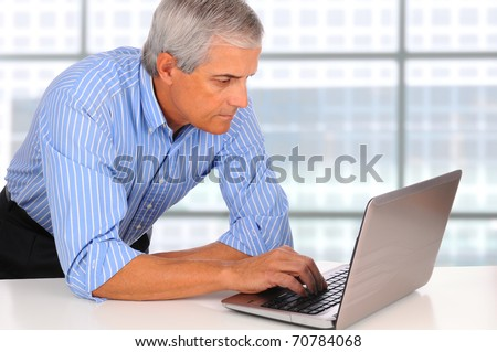 Smiling Middle Aged Businessman leaning on desk using laptop computer with large window background