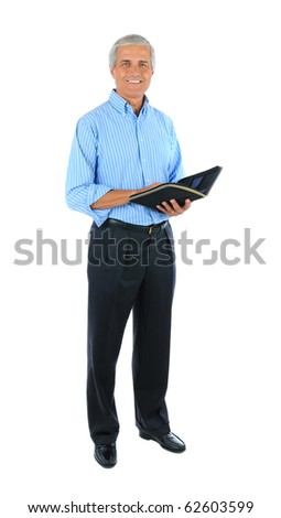 Smiling middle aged businessman standing and holding a notebook . Full length over a white background.