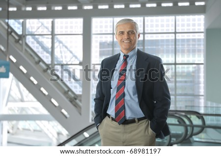 Smiling middle aged businessman standing in the lobby of a modern office building. Man is wearing a blue blazer and khaki pants with hands in his pockets. Horizontal Format.