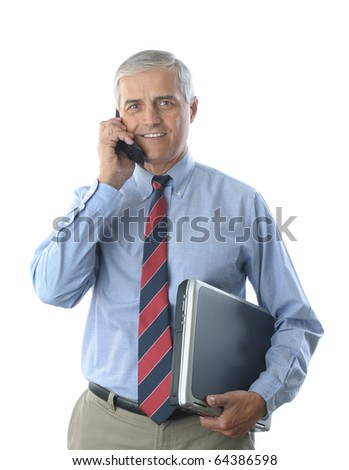 Smiling middle aged businessman talking on a cell phone, and holding a laptop computer under his other arm. Vertical format isolated on white.