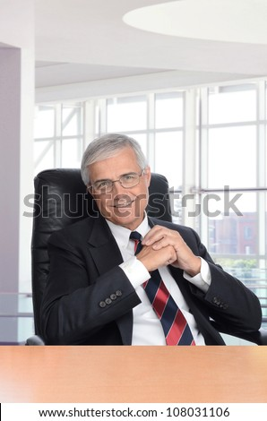 Smiling middle aged businessman with his hands together seated at a desk in a modern office building. Vertical format.