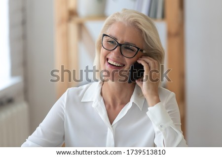 Smiling middle-aged businesswoman have pleasant call or conversation on smartphone gadget with client or partner, happy senior female employee in glasses laugh talking on cellphone at workplace