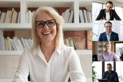 Smiling middle-aged businesswoman talk speak on video call with diverse multiracial colleagues, happy mature female employee engaged in webcam conference or online briefing with coworkers