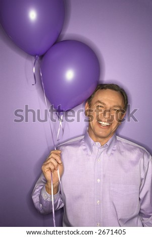 Smiling middle-aged Caucasian man on purple background holding purple balloons.