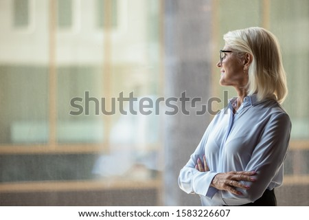 Smiling middle-aged female boss or ceo look in distance window thinking or planning future success, thoughtful motivated mature businesswoman pondering over new ideas, business vision concept