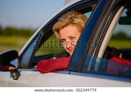 Smiling middle-aged female driver poking her head out of the open side window and turning to smile at the camera