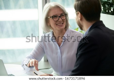 Smiling middle-aged female employee talk brainstorm with male colleague at office briefing in boardroom, happy diverse coworkers have fun laugh cooperating discussing ideas at meeting