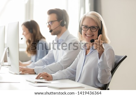 Smiling middle-aged female telemarketer operator work in shared office look at camera show thumb up, happy woman call canter agent consult clients online recommend customer service or helpline