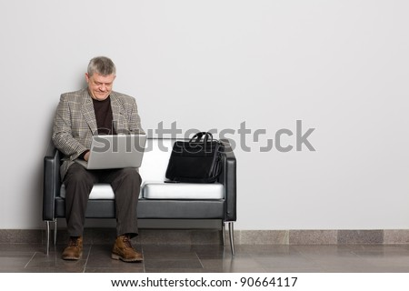 Smiling middle aged man using a laptop in the waiting room.