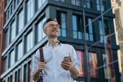 Smiling middle aged man using smartphone, standing on the street. Mobile banking concept. Portrait of handsome mature businessman holding messenger bag, wearing stylish eyeglasses looking at camera