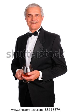 Smiling middle aged man wearing a tuxedo and holding a cognac glass. Vertical format isolated on white