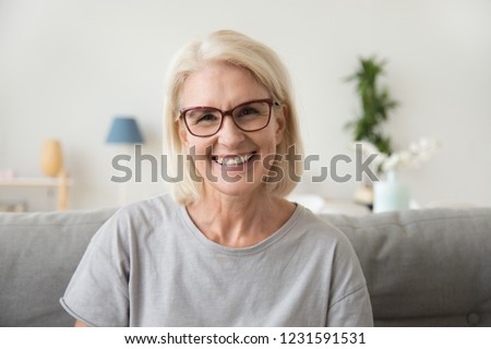 Photo of Smiling middle aged mature grey haired woman looking at camera, happy old lady in glasses posing at home indoor, positive single senior retired female sitting on sofa in living room headshot portrait