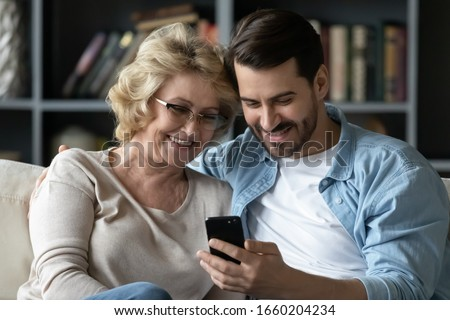 Smiling middle-aged 60s mother rest with grown-up son using smartphone together, happy young man enjoy family weekend with senior mom browsing wireless Internet on cellphone, have fun at home