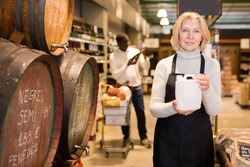 Smiling middle aged saleswoman standing with plastic can near wooden barrels in store, offering wine on tap