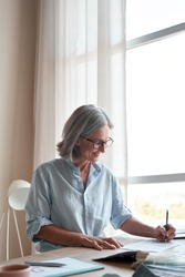 Smiling middle aged stylish woman fashion designer drawing sketches in studio. Mature old adult elegant grey-haired lady dressmaker small business owner creating new fashion design cloth in atelier.